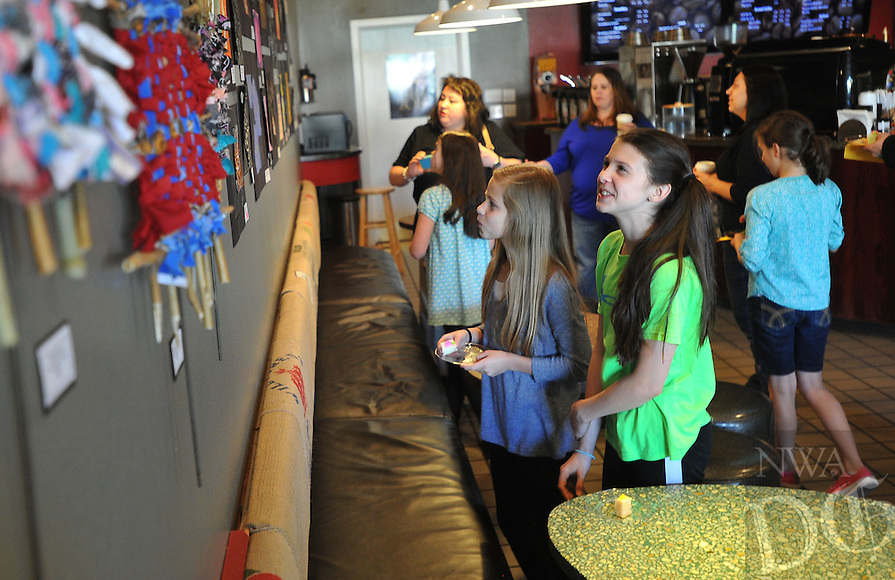 NWA Democrat-Gazette/Michael Woods --04/21/2015--w@NWAMICHAELW... McNair 6th graders Bella Lieklak (left) and Kate Gosnell, take a look at the art on display during the Middle School Art Show & Sale at the Red Kite Coffee Co. in Fayetteville Tuesday evening.  The show features work of students from Holt and McNair middle school and will be on display until  April 29.
