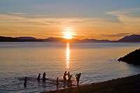 A family enjoys a dip in the chilly water of the Tongass Narrows, near Ketchikan, on a summer evening, southeast, Alaska.
