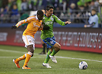 Houston Dynamo defender Kofi Sarkodie battles Seattle Sounders FC defender Leonardo Gonzalez  during play at Qwest Field in Seattle Friday March 25, 2011. The match ended in a 1-1 draw.