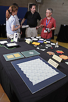 Ralf Konrad, Germany, chats with Orgami friends by his exhibitionb table at the OrigamiUSA 2013 Convention in New York.