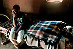 Domfikile Tibe lies sick in her bed as her son Spamale takes care of her in their home on July 2, 2001 in Murchison, a rural area in Natal, South Africa. Domfikile is suffering from an Aids related disease, and she's bedridden most of the time. South Coast Hospice, a local hospice, visits patients in their homes and gives them counseling and emotional support. South Africa has one of the highest infection rates in the world, and about 5.6 million people were HIV positive in 2003. (Photo by: Per-Anders Pettersson)