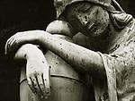 A resting statue in cemetery in sad repose