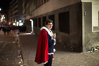 On the second night of festivities a participant in Fasnacht, the Carnival of Basel, takes a break along a sidewalk in the old town of Basel, Switzerland. Feb. 24, 2015.
