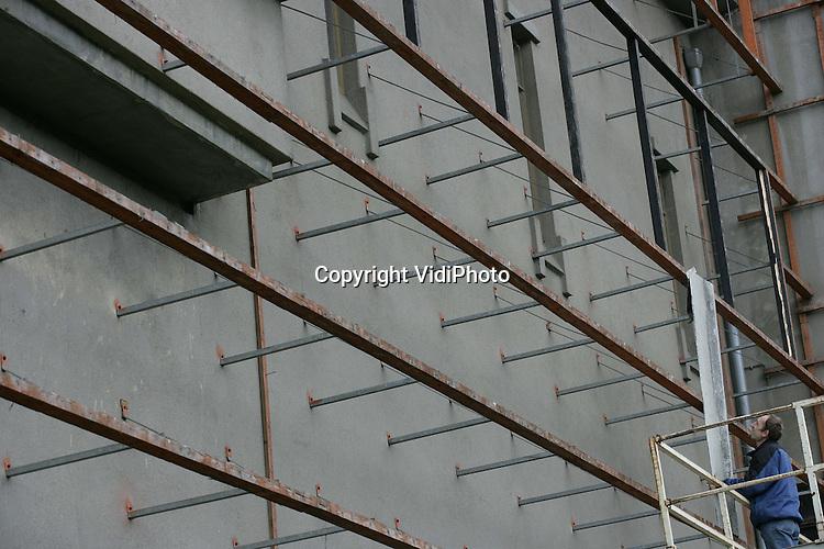 Foto: VidiPhoto..APELDOORN - De voormalige hoogspanningsgebouwen van de NUON in Apeldoorn krijgen een nieuwe bestemming. Daarvoor wordt de ontsierende beplating op de gebouwen van architect Fels, huisarchitect van de voorloper van de NUON (PGEM) verwijderd door slopersbedrijf G. E. van Dam uit Rhenen. Fels ontwierp de gebouwen volgens de filosofie van de Haagse School in baksteen. Later werd een stuclaag aangebracht. De monumenten worden herontwikkeld en in exploitatie genomen door BOEi, de Nationale Maatschappij tot Behoud, Exploitatie en Ontwikkeling van Industrieel Erfgoed. Het 10 kV-gebouw krijgt een bestemming als woon-werkgebouw. Het 50 kV-gebouw krijgt een bestemming als bedrijfsverzamelgebouw. De investeringen bedragen ongeveer 2,5 miljoen euro.