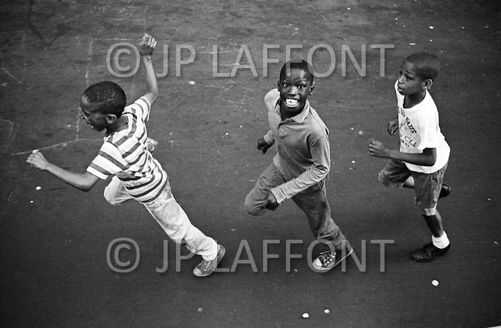 Manhattan, New York City, NY. July 1966. <br /> Three kids running enthusiastically on the streets of Harlem next to the Jazz Mobile, which has been abandonned ever since. It slowly drove in the streets of Harlem and brought  a little joy the people on the sidewalks.<br /> <br /> New York City, Harlem, Juillet 1966: Trois jeunes suivent avec enthousiasme le programe: Jazz Mobile qui a ete abandonne depuis. C'etait un camion qui parcourait lentement les rue d'Harlem l'&eacute;t&eacute; pour apporter un peu de joie sur les trottoirs!