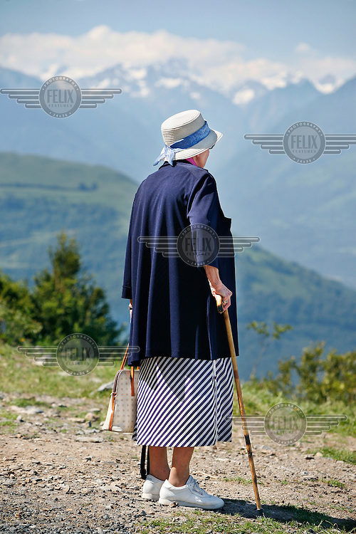 An elderly woman looks out over the French Pyrenees and the city of Lourdes, one of the most popular Catholic pilgrimage sites in the world. In 2008 Lourdes celebrated the 150 year anniversary of the apparitions of Our Lady of Lourdes who appeared to Bernadette Soubirous in 1858.