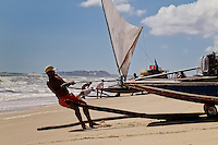 A Brazilian fisherman (jangadeiro) pushes the boat on the beach of Prainha, Ceará state, northeastern Brazil, 8 March 2004. Jangadeiros, working on a unique wooden raft boat called jangada, keep the tradition of artisan fishing for more than four hundred years. However, being a fisherman on jangada is highly dangerous job. Jangadeiros spend up to several days on high-sea, sailing tens of kilometres far from the coast, with no navigation on board. In the last two decades jangadeiros have been facing up the pressure from motorized vessels which use modern, effective (and environmentally destructive) fishing methods. Every time jangadeiros come back from the sea with less fish.
