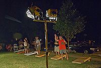Players at night at cornhole tournament in a neighborhood