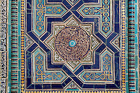 """Detail of octagonal star decoration, """"Nameless 1"""" Mausoleum, 1380s, Shah-I Zinda ensemble, Samarkand, Uzbekistan, pictured on July 19, 2010, in the morning. The Shah-i-Zinda Complex is a necropolis of mausoleums whose legendary origin dates back to 676 when Kussam-ibn-Abbas arrived to convert the locals to Islam. So successful was he that he was assassinated whilst at prayer. His grave remains the centre of the sacred site which grew over many centuries, especially the 14th and 15th, into an architecturally stunning  example of ceramic art. This Mausoleum, created by Usto Alim Nesefi, is decorated  with relief painted majolica. The portal decorations are notable for the symbol of """"octagonal stars"""". Samarkand, a city on the Silk Road, founded as Afrosiab in the 7th century BC, is a meeting point for the world's cultures. Its most important development was in the Timurid period, 14th to 15th centuries. Picture by Manuel Cohen."""