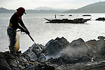 A worker sprays rocks along the shoreline in Botongon, a neighborhood of Estancia, Philippines, in an effort to remove oil that spilled there when Typhoon Haiyan swept through the area in November 2013. The storm was known locally as Yolanda. Most residents who lived along the affected coastline remain camped in temporary shelters elsewhere, despite government efforts to get many to return. The ACT Alliance is accompanying them as they struggle to survive.