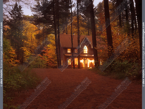 Brick country house or cottage with lights on in colorful autumn evening twilight nature scenery in Muskoka, Ontario, Canada countryside.