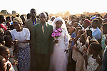 MPHANDULA, MALAWI - AUGUST 19: Betino Phipi, age 21, walks with Suzana Nabanda, age 16, his new wife, on August 19, 2006 in Mphandula village, about 30 miles outside Lilongwe, Malawi. Mr. Phipi, a farmer, just got married a few hours earlier and he is showing his wife to the villagers. Mphandula is a poor village in Malawi, without electricity or clean water. Nobody owns a car or a mobile phone. Most people live on farming. About 7000 people live in the village and the chief estimates that there are about five-hundred orphans. Many have been affected by HIV/Aids and many of the children are orphaned. A foundation started by Madonna has decided to build an orphan center in the village through Consol Homes, a Malawi based organization. Raising Malawi is investing about 3 million dollars in the project and Madonna is scheduled to visit the village in October 2006. Malawi is a small landlocked country in Southern Africa without any natural resources. Many people are affected by the Aids epidemic. Malawi is one of the poorest countries in the world and has about 1 million orphaned children. (Photo by Per-Anders Pettersson)