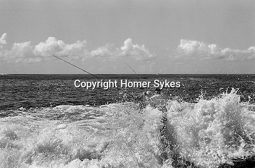 Father and son fishing off rocks Bondi beach headland, Sydney Australia.