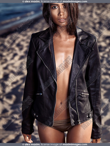 Sexy young woman shiny sun tanned skin wearing a black leather jacket at the beach