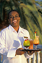 Waitress Esther Alee, Sunset Waters Beach Resort, with cocktails made with Curacao liqueur; Curaçao, Netherlands Antilles...