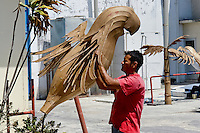 A Colombian man works on the allegorical statue of a parrot in front of the Carnival workshop, Barranquilla, Colombia, 23 February 2006. The Carnival of Barranquilla is a unique festivity which takes place every year during February or March on the Caribbean coast of Colombia. The allegorical floats and masks are created by artists with their teams. These crews are highly specialized to design and create large floats because they keep this profession in the family for decades.