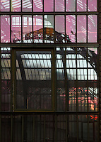 The New Caledonia Glasshouse (formerly The Mexican Hothouse), 1830s by Charles Rohault de Fleury, Jardin des Plantes, Museum National d'Histoire Naturelle, Paris, France, in which is reflected the Plant History Glasshouse (formerly the Australian Glasshouse), 1830s, Charles Rohault de Fleury. Detail of the glass and metal structures in the late afternoon light. The New Caledonia Glasshouse, or Hothouse, was the first French glass and iron building.