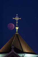 The blood moon sets behind the cross at the top of St. Paul the Apostle Catholic Church in Westerville, OH.