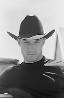 Portrait of a young man wearing a black cowboy hat