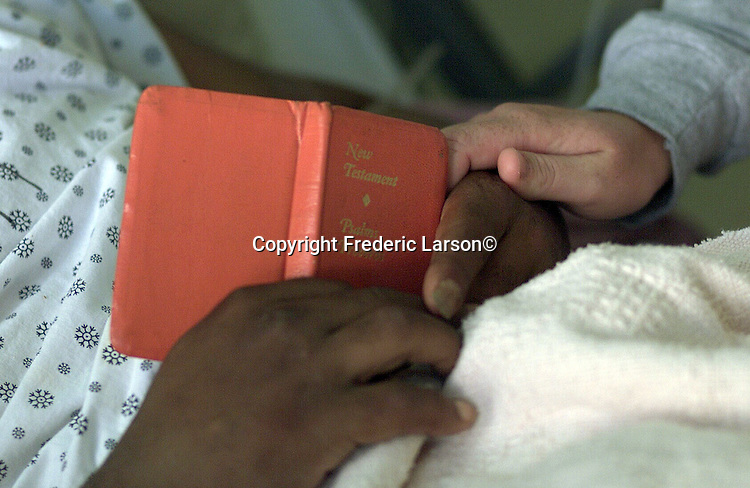 Chaplain Ann Moore read the bible to patient Henry Eric on the AIDS ward Of San Francisco General Hospital, California.