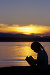 Young girl silhouetted reading a book on the beach at sunset