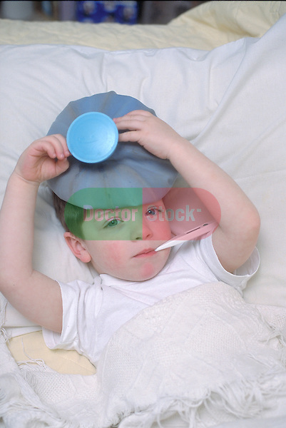 sickly 4 year old boy lying in bed with thermometer in mouth and ice bag on his head, common cold