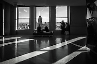 People enjoy the view of the Empire State Building from the window of the Top of the Rock