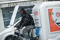 A man driving a bicycle operated post and parcel delivery van in the snow in Paris, France.