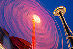 Seattle Space Needle and a carnival ride at the Seattle Center with the Experience Music Project building in the background