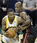 Seattle Supersonics' Rashard Lewis ,left, is held by Miami Heats' Antoine Walker as he drives to the basket in the fourth quarter at Key Arena in Seattle, Washington  on Friday, 13 March 2005. Lewis scored 33 points in the Supersonics 104-117 loss to the Heat.  Jim Bryant Photo. &copy;2010. All Rights Reserved.