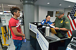 Edwin Chacon, an asylum seeker from Honduras, watches as TSA agent Norma Villegas and Border Patrol agent Rene Perez inspect his papers in the Valley International Airport in Harlingen, Texas. Chacon was transported to the airport by the Posada Providencia in San Benito, where Chacon, 18, stayed for several days after being released by immigration authorities pending a judicial hearing on his asylum request. He was on his way to stay with a relative elsewhere in the United States.<br /> <br /> Sponsored by the Catholic Sisters of Divine Providence, the Posada Providencia provides a safe place for people in crisis from all over the world who are seeking legal refuge in the United States.