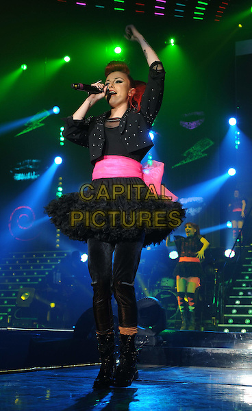 CHER LLOYD.The X Factor Live tour, Wembly Arena, London, England,.March 6th 2011.performance music concert gig on stage full length singing microphone black leggings ra-ra tutu skirt pink sash jacket singing top boots patent leather hand arm in air  .CAP/WIZ.© Wizard/Capital Pictures.