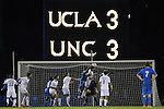 06 December 2014: North Carolina's Rob Lovejoy (16) heads the ball in overtime as the scoreboard shows the score. The University of California Los Angeles Bruins hosted the University of North Carolina Tar Heels at Drake Stadium in Los Angeles, California in a 2014 NCAA Division I Men's Soccer Tournament Quarterfinal round match. The game ended in a 3-3 tie after two overtimes. UCLA advanced to the next round by winning the penalty kick shootout 7-6.