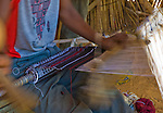"""A weaver at the National Museum in Niamey, Niger weaves strips of cloth that will be made into placemats, or that will be sewn together to make a Fulani """"wedding blanket."""""""