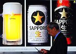 A man walks past a poster advertising Sapporo Breweries Ltd.'s beer