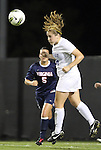 29 September 2011: Duke's Maddy Haller (right) heads the ball away from Virginia's Olivia Brannon (5). The Duke University Blue Devils and the University of Virginia Cavaliers played to a 0-0 tie after overtime at Koskinen Stadium in Durham, North Carolina in an NCAA Division I Women's Soccer game.