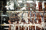 An old brick wall of a ruined house with faded characters and color layers.