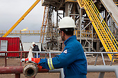 BAGHDAD, IRAQ: Workers role a pipe a the drilling tower of well number 7 at the Midland Oil Company field.