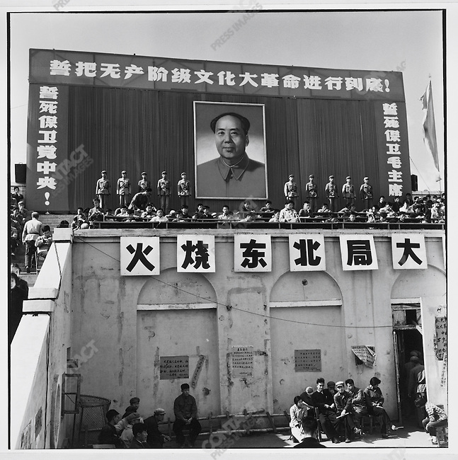 "A rally at Red Guard Square (the renamed People's Stadium) calls for the ""burning of the Northeastern Bureau"" (large characters in center); banners read: (top) ""We swear to carry out the great Proletarian Cultural Revolution to the end""; (left) ""We will die to protect the Communist Party Central Committee"" and (right) ""We will die to protect Chairman Mao""; Harbin, Heilongjiang Province, August 17, 1966"