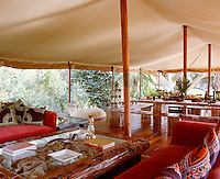 The 'living' tent is furnished with comfortable sofas and a rudimentary table with rustic wooden benches
