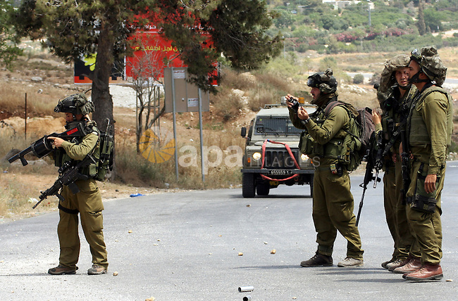 Israeli soldiers prepare to fire tear gas canisters during clashes with Palestinian protestors in the West  Bank village of Nabi Saleh, on 28 May 2010. Palestinians protest weekly against the neighbouring Jewish settlement of Halamish. photo by Eyad Jadallah