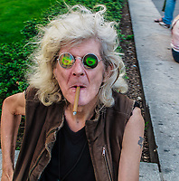 Older man with long grey hair, no teeth, smoking little cigar, wearing weird goggle eye glasses.