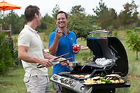 Two men enjoying time outdoors by a barbecue