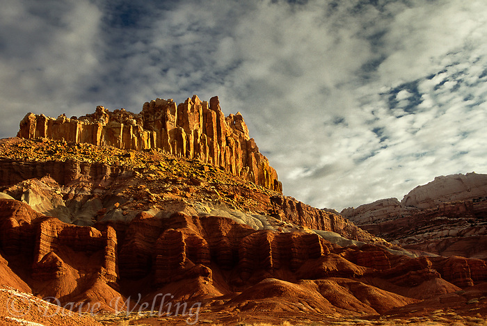 731350066 sunrise lights up the brilliant red and gold sandstone formations of the castle in capitol reef national park utah