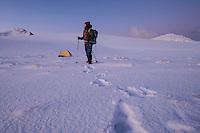 Female hiker stands near winter camp, Ytresandheia, Moskenesøy, Lofoten Islands, Norway