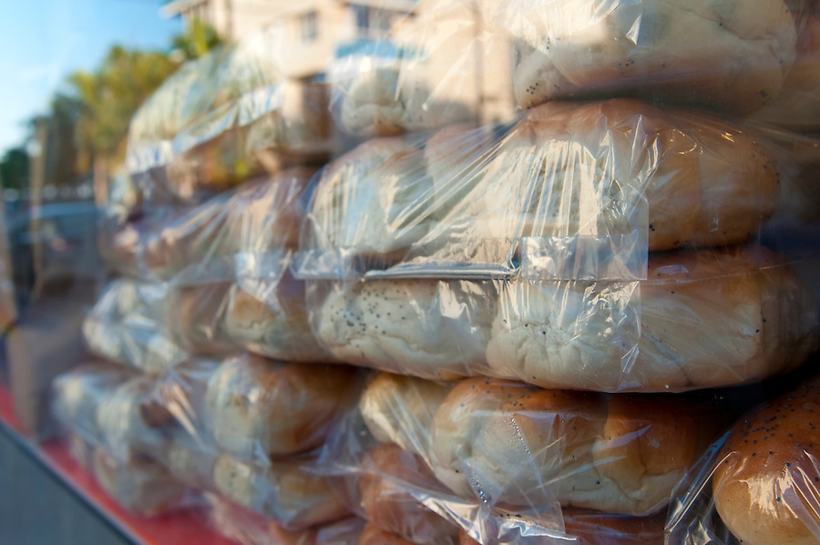 View of row of recently baked bread buns in bags ready to be sold through store window.