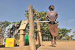In the Southern Sudan village of Kupera, a girl pumps water from a well installed by Catholic Relief Services (CRS). Families here returned from refuge in Uganda in 2006 following the 2005 Comprehensive Peace Agreement between the north and south.