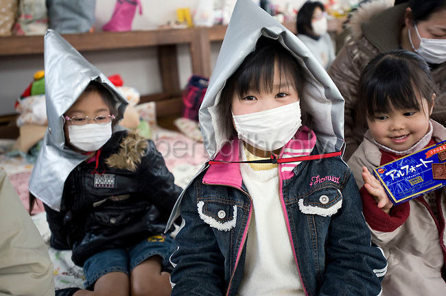 Yui Komatsu (2r) and her sister Yume pose with garb to protect them in times of earthquakes at a refugee shelter in  Miyagi Prefecture, Japan on 13 March, 2011. Photographer: Robert Gilhooly