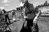 A cowboy readies his protective vest and ropes before competing in the bullriding competition at the annual Lincoln Rodeo in Lincoln, MT in June 2006.  The Lincoln Rodeo is an open rodeo, which means competitors need not be a member of a professional rodeo association.