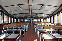 The timeless interior of the upper deck of a Star Ferry, with reversible seating and perforated star emblems in some seats